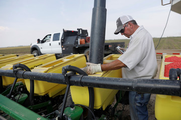 Farmer Bruce Elder, 56, a farmer for 40 years, fills a seeding container with soybean seeds in Gideon, Missouri