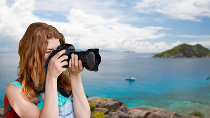 travel, tourism and photography concept - happy young woman with backpack and camera photographing over background of seychelles island in indian ocean