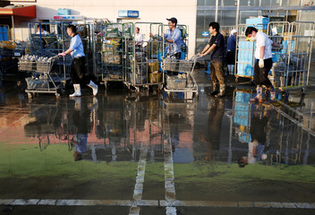 Employees of a supermarket push trolleys and shelves, with muddy items, at their store in a flooded area in Mabi town in Kurashiki