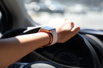 lady drives a car with one hand with a  smart watch on it