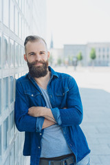 Confident bearded man leaning on a city wall