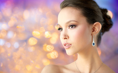 beauty, jewelry, people and luxury concept - close up of beautiful asian woman or bride with earring over holidays lights background