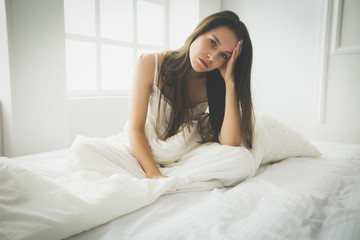 Young female feeling pain in bed.