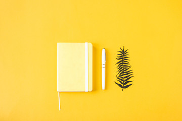 Yellow minimalistic notepad for entries on a yellow background. Planning, keeping a diary, time management concept. Top view, flat lay Wall mural
