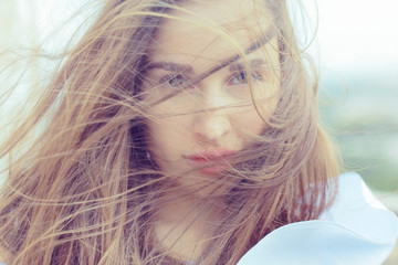 Brunette beautiful disheveled hair portrait on the beach hairstyle