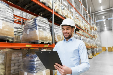 logistic business, shipment and people concept - businessman in helmet with clipboard checking goods at warehouse