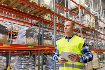 logistic business, technology, shipment and people concept - man or manual worker with tablet pc at warehouse