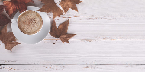 Hot coffee cappucino and autumn leaves on old white wooden background.Seasonal relax concept,flat lay