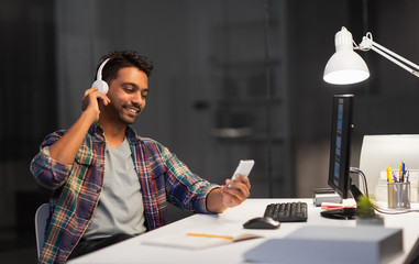 deadline, technology and people concept - happy creative man with headphones listening to music by smartphone and computer at night office