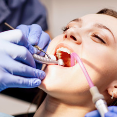 Male dentist treating teeth to young woman patient in clinic.