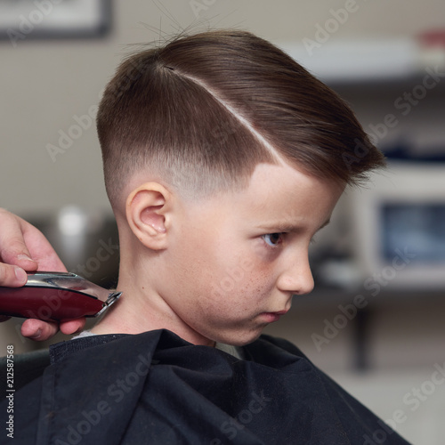 Barber Is Shaving A Hair To Caucasian Boy In Barbershop Stock