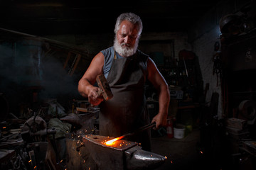 Blacksmith with brush handles the molten metal