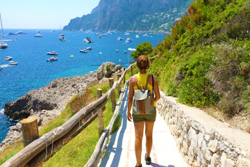 Female hiker go down and descent the pathway with spectacular landscape of Capri, Naples, Italy Wall mural