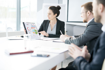 Portrait of beautiful young businesswoman heading meeting sitting at table in conference room and pointing at chart copy space