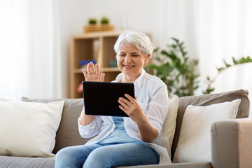 technology, people and communication concept - happy senior woman with tablet pc computer having video chat at home