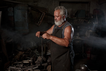 Brutal blacksmith artisan in apron makes the product in the blacksmith