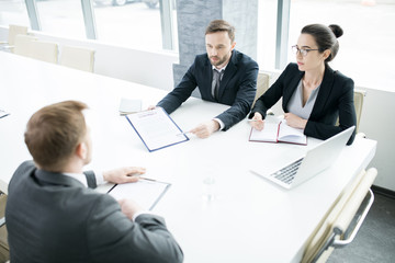 Portrait of three successful business people, man and woman,  talking to partner sitting across meeting table in conference room, copy space
