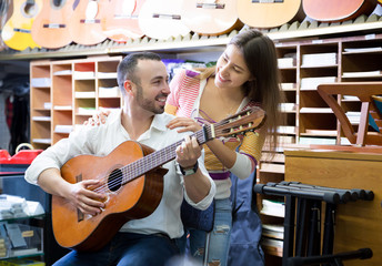 Young couple buying guitar in store