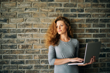 Portrait of woman holding laptop and standing in front of brick wall.