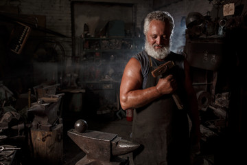 Portrait of a blacksmith artisan with a hammer in a blacksmith