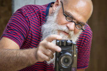 a bearded man taking a photograph