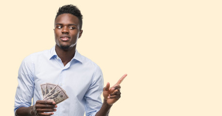 Young african american businessman holding dollars very happy pointing with hand and finger to the side