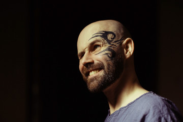 tattoo on the face,  male portrait in the form of an assassin, cosplay,  tattooed brutal man,  guy with a tattooed face
