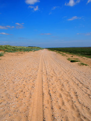 a straight long dry sand road with tire tracks and footprints extending to the horizon surrounded by grass covered dunes with a bright blue summer sky