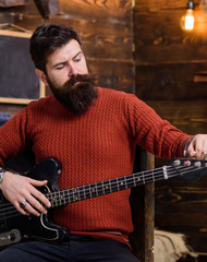 Rock musician with brutal look posing with instrument. Bearded man tuning electric guitar. Man with stylish beard and mustache in terracotta knitted sweater and black jeans relaxing, music concept