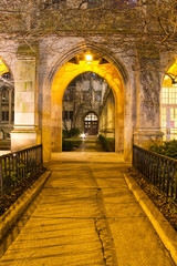 A gothic arch of a church illuminated at night leading into a courtyard.