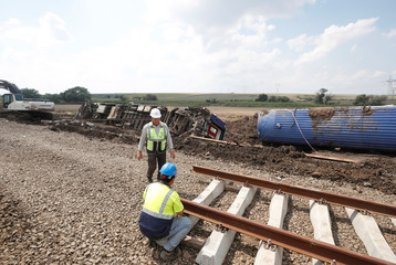 Railway workers stand at the scene where a passenger train derailed on Sunday, near Corlu in Tekirdag province