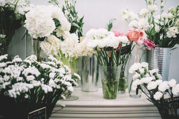 Beautiful fresh blossoming flowers (ranunculus, roses, hydrangea, lisianthus) at the florist shop shelves in the fridge
