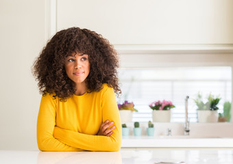 African american woman wearing yellow sweater at kitchen smiling looking side and staring away thinking.