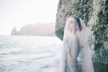 Beautiful brunette girl bride in a grey gown of lace and tulle, covered her face with a veil, hand on breast,