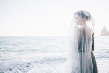 Beautiful woman bride under a veil near the sea. wedding, happiness, lifestyle