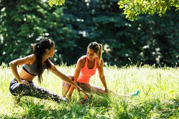 Two young woman stretching and relaxing after jogging outdoor.They stretch her legs and body.