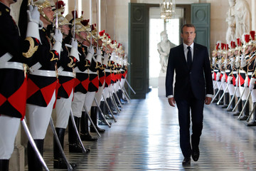 French President Emmanuel Macron walks through the Galerie des Bustes before his address to the upper and lower houses of the French parliament at a special session in Versailles near Paris