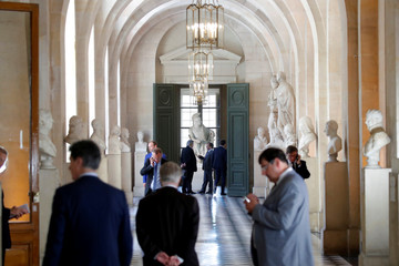 Members of Parliament stand in the Galerie des Bustes (Busts Gallery) before the arrival of French President Emmanuel Macron at a special session in Versailles near Paris