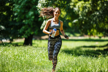 Young happy  woman jogging outdoor at the park .Green environment and spring concept.