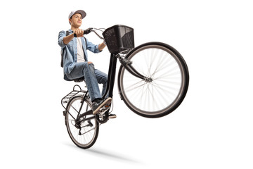 Teenager doing a wheelie with a bicycle