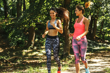 Two young female friends jogging at the woods.Easy running and talk.