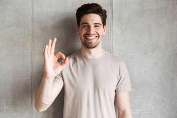 Cheerful young man showing okay gesture.