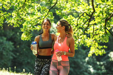 Two young female friends jogging at the woods.Embrace each other and laughing.