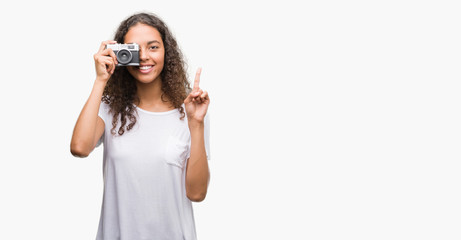 Young hispanic woman taking pictures using vintage camera surprised with an idea or question pointing finger with happy face, number one