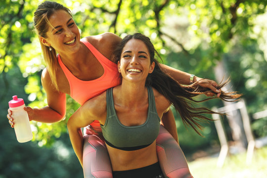 Two best female friends making fun after jogging and workout.They laughing and carrying each other.