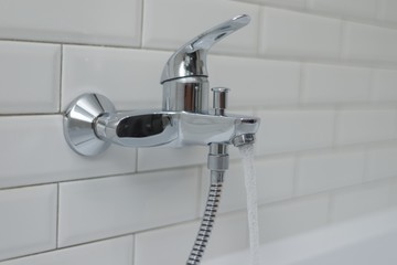Close-up of an open chrome faucet mixer in bathtub with running water