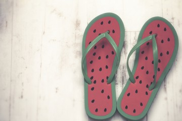 flip flops with print of a watermelon on white wooden background
