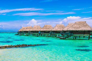 Luxury beach travel vacation concept: Overwater bungalows on turquoise coral reef lagoon ocean close to the beach.
