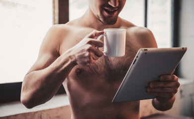 Close up. Bare-chested Man with Tablet and Coffee.