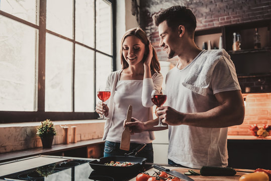 Young Couple Cooking Dinner and Drink Red Wine.